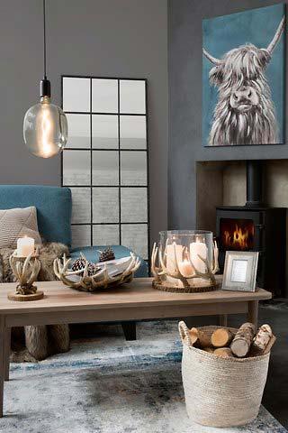 Mesa con decorados de madera de estilo rural con cornamenta de venado con chimenea de gas