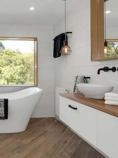 Baño con baldosa blanca suelo de madera y bañera clásica de aluminio