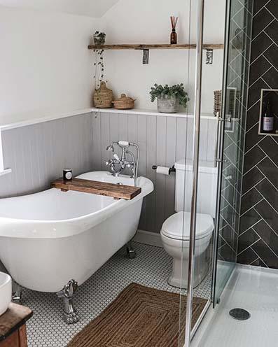 Baño con suelo hexágonos pared de madera y yeso blanco. Bañera clásica con accesorios de madera