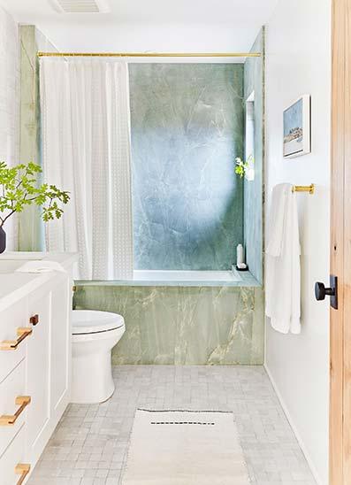 Baño moderno de mármol con grifería doble dorada con suelo de cerámica