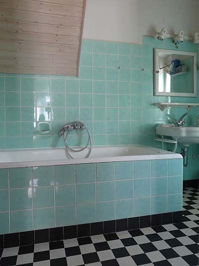 Bañera de estilo moderno con suelo y pared de madera estilo parquet con grifería y aseo blanco y muebles empotrados