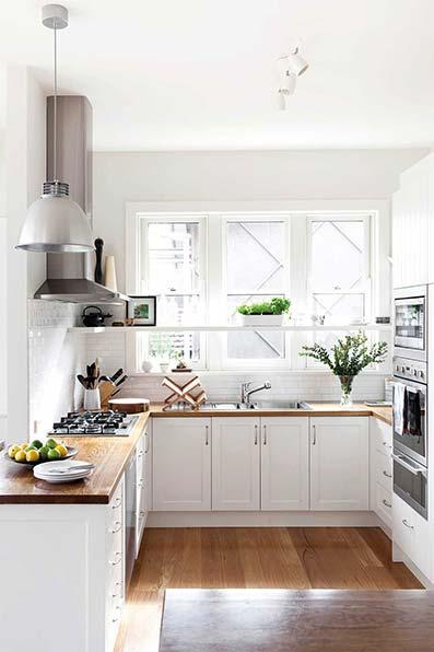 Cocina con suelo de parquet encimera con muebles de madera blanco. techo y paredes blancas