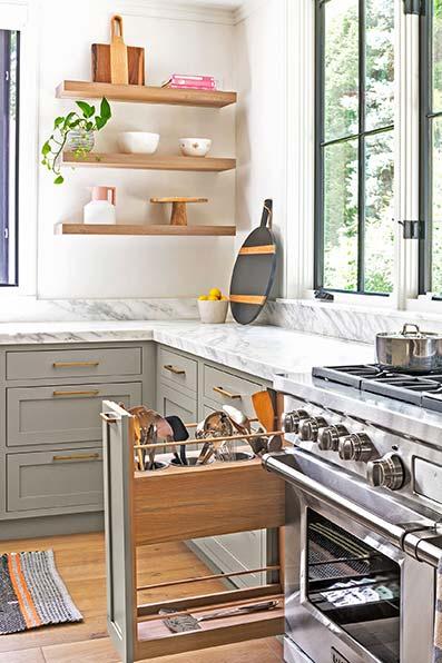 Cocina con electrodomésticos y cubertería. Encimera de mármol y suelo de madera