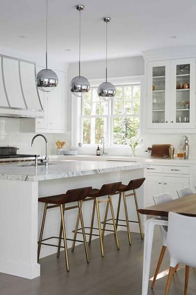 Cocina americana con isla en medio con grifería y taburetes. Muebles, paredes y techo blanco estilo victoriano. Suelo de madera brillante marrón oscuro