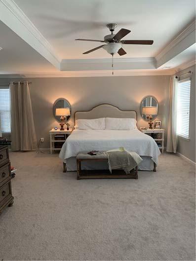 Dormitorio amplio con techo victoriano ventilador de techo moqueta beige con cama grande tipo isla