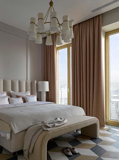 Dormitorio piso cama con canapé y suelo de mosaico con cortinas rosas claro