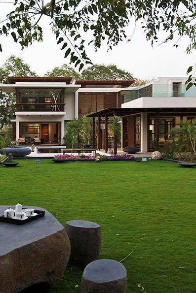 jardín moderno con césped cortado con piedras decorativas en casa moderna modular