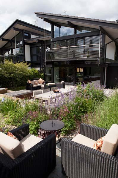 Jardín con pequeños arbustos aromáticos con sillas de mimbre de diseño y pequeña charca en el centro