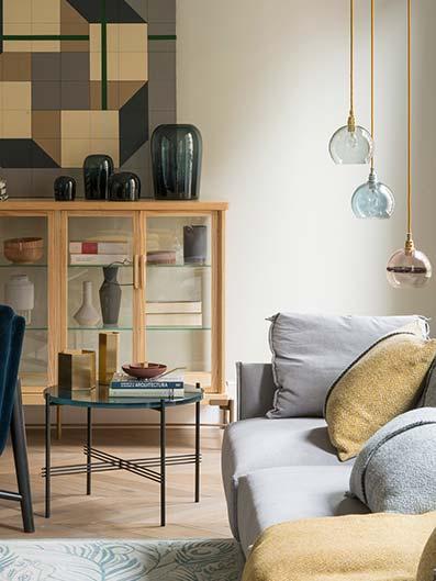 Sala de estar con mesa redonda y sillas con chimenea y suelo de madera con estanterías con libros