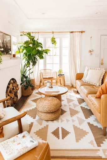 Salón con sillón de rinconera paredes beige con moqueta gris de estilo mosaico.