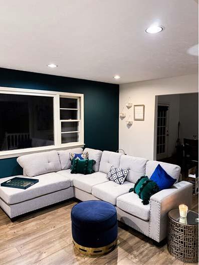 Salón vanguardista con sofá en isla con rinconeras. Pared verde metálica y luces led empotradas