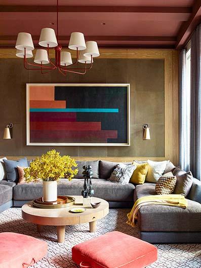 Salón clásico con sofá de tela azul pastel con alfombra morada con mosaicos. Pared blancas con techo blanco