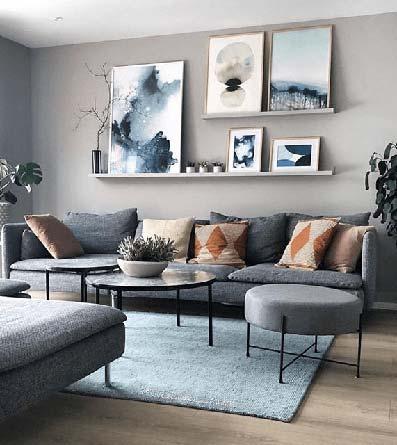 Salón con sofá en pared alfombra azul de pelo con cuadros en estantería