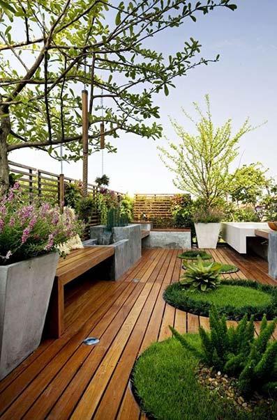 Jardín con parquet con macetas grandes de arbusto y diseños modernos con césped