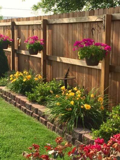 Vallas para jardín de madera con macetas florales de temporada con césped cortado