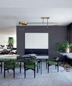 El color gris en pintura antracita en la cocina abierta o alicatado en el comedor, resalta el mobiliario, las sillas verdes y la mesa de vidrio.