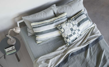 decoración del dormitorio en una hermosa armonía de gris pastel y blanco.  El parquet, las paredes están pintadas del mismo gris suave, la ropa de cama retoma el tema del gris en tonos un poco más intensos.  Las fundas de almohada de rayas y cuadros aportan un toque de fantasía a este universo monocromático