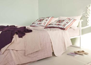 Decoración de dormitorios en armonía de tonos pastel.  En las paredes, una pintura verde jade asociada a la ropa de cama en colores diluidos.  Cojín de cama de lino rosa suave, fundas de almohada de cuadros blancos, rosa suave y rosa intenso