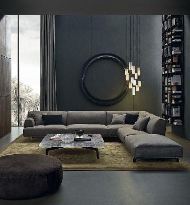 El gris del gran sofá destaca en la atmósfera antracita contemporánea que da el cuadro.  El piso de concreto encerado se suma al aspecto gris intenso de esta sala de estar.