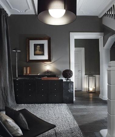 Un mosaico de antracita en el suelo y una pintura de color gris oscuro, esta pequeña sala de estar utiliza el color gris en total look para resaltar el lado elegante y lujoso de los muebles.