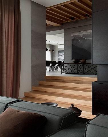 En un salón moderno y hasta el pasillo, el color gris difunde sus matices.  El diseñador de color gris marengo pintado en las paredes coincide con los escalones de la escalera de madera.