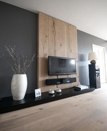 La madera y el gris carbón para la decoración de una sala de estar es un matrimonio que funciona.  En esta sala de estar de diseño, el mueble de TV y el largo estante lacado en negro se destacan por el panel de madera colocado en la pared gris intenso.