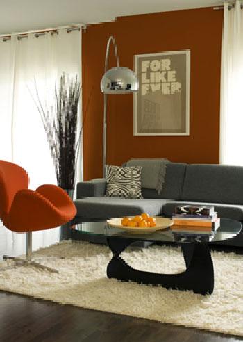 Un sillón de diseño naranja, un sofá gris y una alfombra color crudo, una paleta de colores moderna y moderna para la sala de estar, fieltrada y dinámica.
