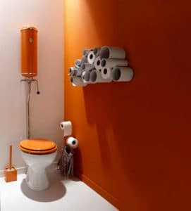 WC Deco.  Pintura color naranja y blanco Almacenamiento de papel higiénico en tubos de PVC.