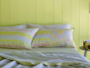 Decoración de dormitorios en tonos pastel.  Pintura de pared, sábana, cuadros y almohada de color verde suave Little Greene de la colección Spring Society