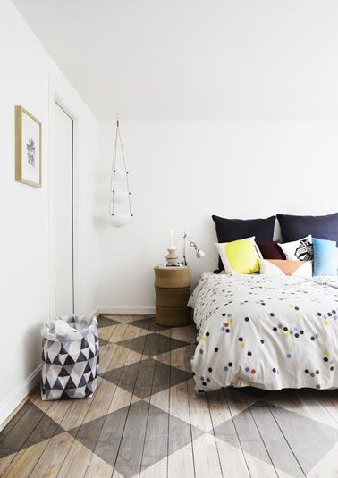 Suelo de parquet para dormitorios de adultos, renovado con pintura, en grandes patrones de azulejos a cuadros gris-marrón.  la veta del parquet se deja visible para una atmósfera más sutil