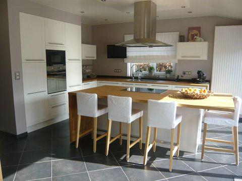 La isla central, en esta gran cocina abierta al salón, pide convivencia.  Una decoración moderna con colores suaves y naturales para una acogedora cocina abierta
