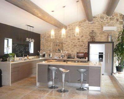 Un estilo rústico con vigas a la vista y piedras mezcladas con una decoración y colores de moda, ¡aquí hay uno bueno para esta hermosa cocina abierta!