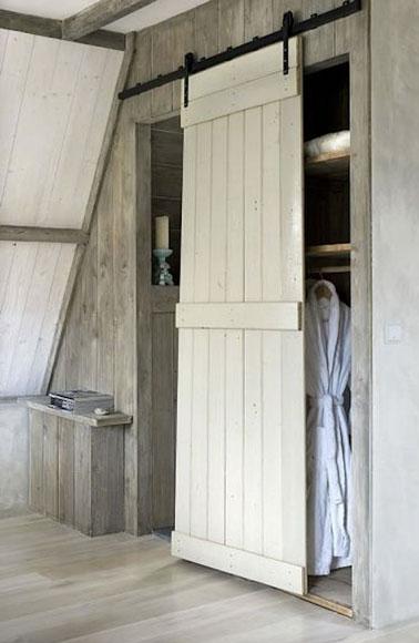 Ejemplo de mampara corredera realizada con contraventana para cerrar un vestidor de ático.  Repintado con pintura blanca, la puerta ilumina toda la habitación.