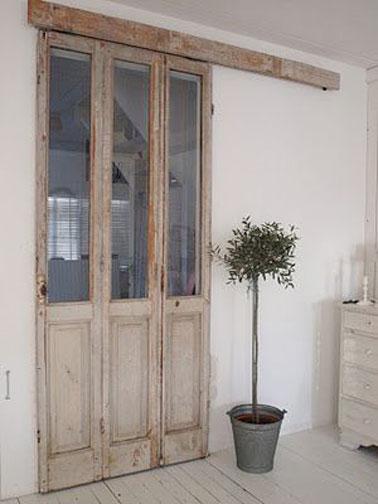 Una mampara corredera hecha con una ventana francesa de madera patinada inspira una decoración provenzal en esta entrada blanca.  Mezclado con un parquet blanco lazuré estructura el espacio