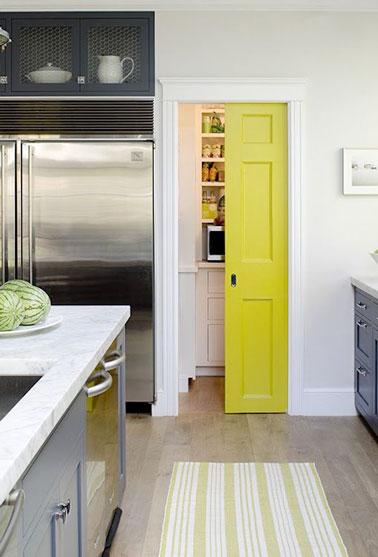 Una partición corrediza de color amarillo brillante colorea la cocina abierta y cierra un armario de almacenamiento en una decoración contemporánea.  A juego con el suelo, se ve reforzado por las paredes blancas.
