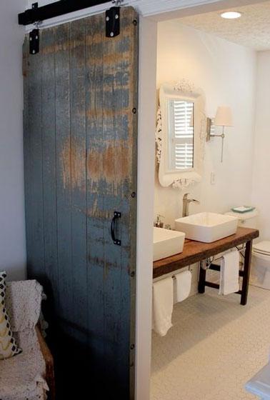 Una puerta recuperada utilizada como partición corredera marca el tono de la decoración auténtica de este pequeño baño blanco.  Conservado en su propio jugo, solo se barniza