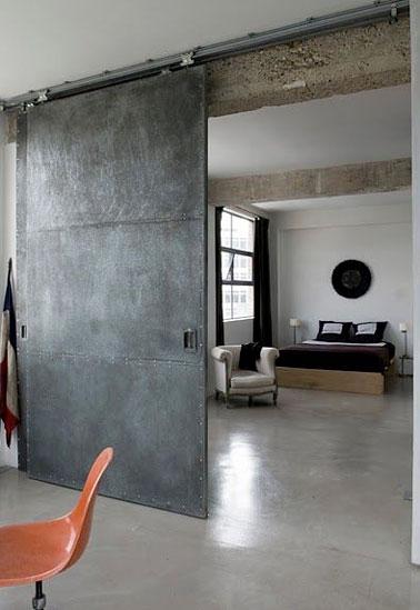 Decoración industrial en el dormitorio principal con este tabique corredero realizado a partir de una puerta reciclada tratada con un yeso efecto cemento para aislar el dormitorio del salón