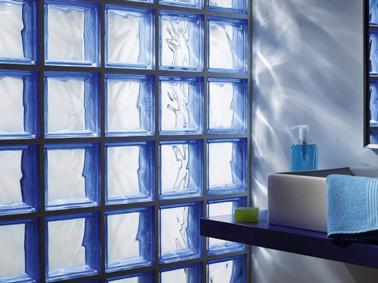 Tabique de ladrillo de vidrio blanco con juntas azules en baño.  Encimera y pintura de pared azul a juego