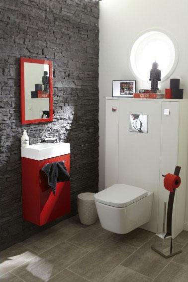 Apostando por la diferencia en los revestimientos y la elegancia del gris antracita y el rojo de los elegantes inodoros compuestos por un muro de piedra enfrentada y una gran losa para rodear el espacio de la taza del inodoro suspendida pintada en blanco.  En contraste, un lavabo, un espejo y papel higiénico rojo vivo.
