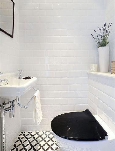 En los aseos sin ventanas, losas blancas de metro colocadas en toda la altura de las paredes iluminadas por los patrones negros de los mosaicos del suelo que resuenan con el asiento del inodoro del lavabo suspendido.