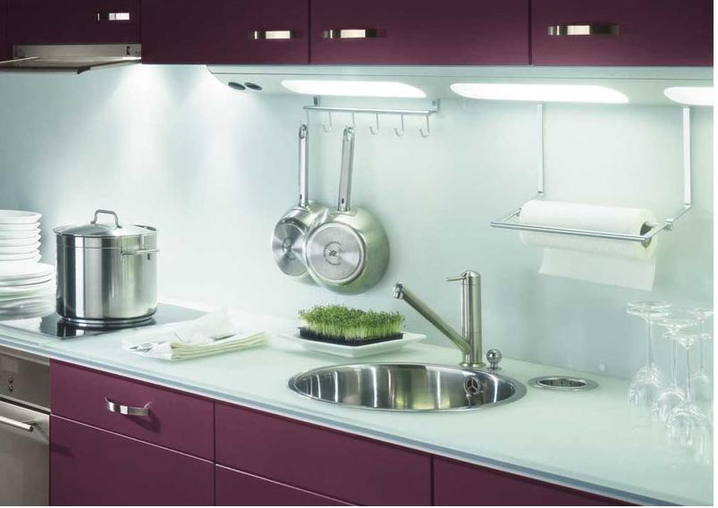 Encimera de cocina Luisina y salpicadero de vidrio instalados en una cocina berenjena.  La barra de luz sobre la encimera aumenta el efecto de luz del vidrio.