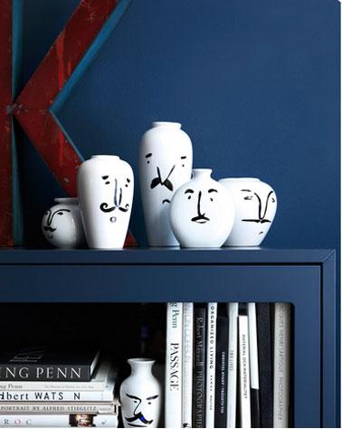 Para ampliar la sala de estar, la biblioteca y las paredes están pintadas en el color azul Mónaco.  La serie de jarrones blancos aporta un fuerte contraste.