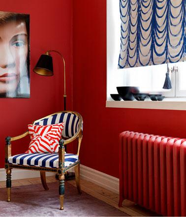 Una sala de estar decorada en un ambiente tocador contemporáneo.  Pintura de pared de color rojo brillante, cortina azul y sillón blanco estilo tapizado de tela a rayas blancas y azules