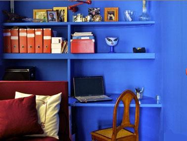 Espacio de oficina creado en una sala de estar con repisa y pared pintadas en azul intenso.  silla y accesorios de oficina en naranja para crear un contraste fuerte y cálido