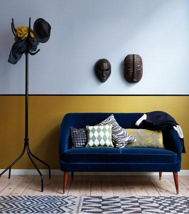 Sala de estar de diseño africano con paredes de pintura azul, base de pintura amarilla, línea de pintura negra, cojines de tela africana en un pequeño sofá azul Mónaco