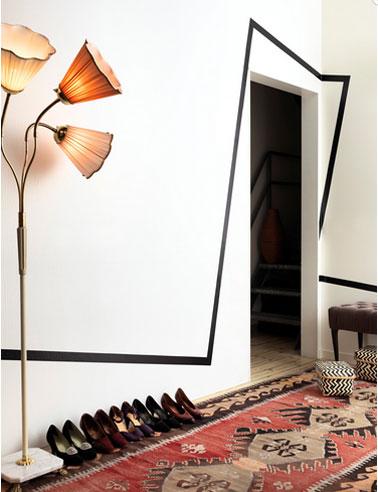 Pintando las paredes del salón en blanco, líneas gráficas negras en la pared y el marco de la puerta.  en el suelo una alfombra Kilim roja en contraste