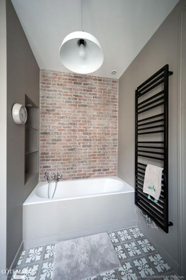 Un baño color topo que combina baldosas de cemento y pared de ladrillo, acondicionado con un nicho, una idea ideal para aumentar el área de almacenamiento de la habitación