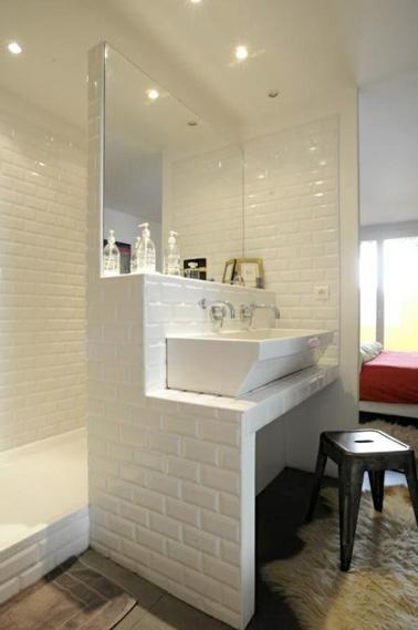 En este pequeño baño con alicatado de metro blanco, ¡apostamos por la pared como espacio de almacenaje!  Una buena idea para una solución de ahorro de espacio que funcione