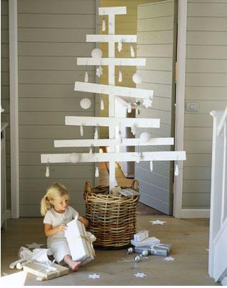 Para una elegante decoración navideña, un árbol de Navidad hecho con tablas de madera pintadas de blanco.  Bolas y adornos en blanco también