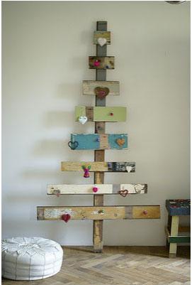 Calendario de Adviento en forma de árbol de Navidad elaborado con cartones reciclados y decorado con pequeños corazones y temas rojos caseros